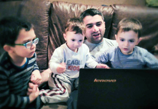 A father and his three sons watching cartoons